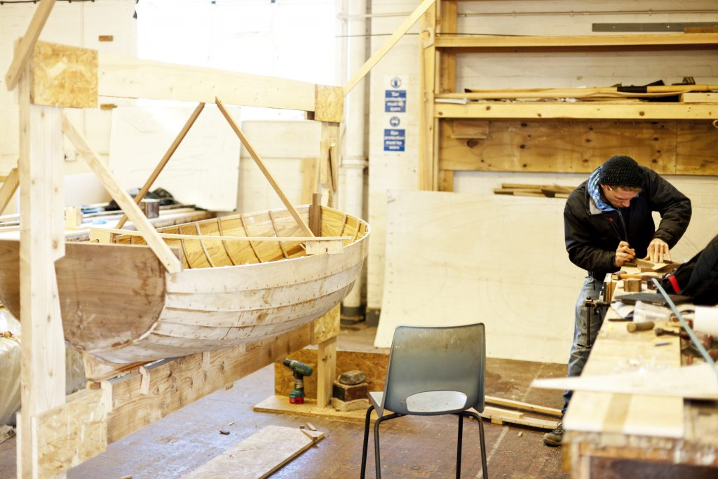 A handcrafted wooden rowing boat is nearing completion. Boat Building Academy, Lyme Regis