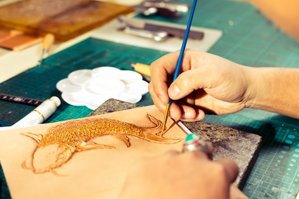 Chinese traditional leatherworker painting fish pattern on the leather